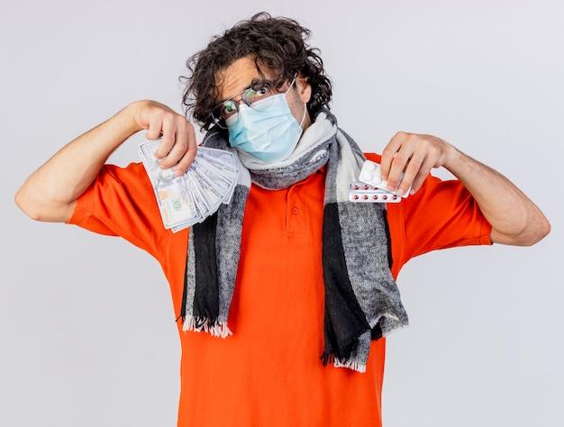 Giovane uomo malato caucasico indossando occhiali sciarpa e maschera che tiene soldi e pillole isolati sulla parete bianca
