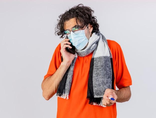 Giovane uomo malato caucasico indossando occhiali sciarpa e maschera tenendo il termometro parlando al telefono isolato sulla parete bianca con lo spazio della copia