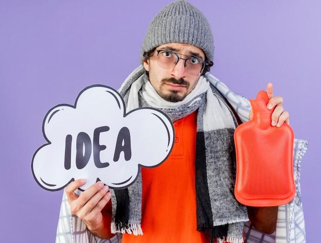 紫色の背景に分離されたカメラを見て、アイデアバブルと湯たんぽを保持している格子縞に包まれたメガネ冬帽子とスカーフを身に着けている若い白人の病気の男