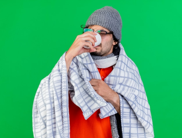 Young caucasian ill man wearing glasses winter hat and scarf wrapped in plaid grabbing plaid looking inside cup drinking tea isolated on green wall