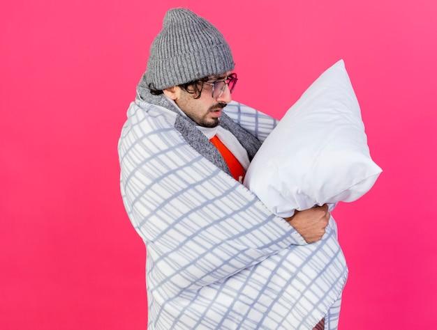 Giovane uomo malato caucasico con gli occhiali cappello invernale e sciarpa avvolti in plaid in piedi in vista di profilo tenendo e guardando il cuscino isolato sulla parete cremisi con lo spazio della copia