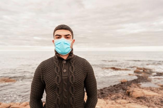 코로나 바이러스 안전 보호 마스크를 쓰고 겨울 스웨터에 젊은 백인