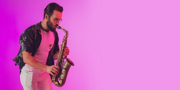 Молодой кавказский джазовый музыкант играет на саксофоне в неоновом свете, флаер с copyspace для рекламы