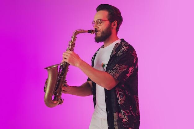Молодой кавказский джазовый музыкант играет на саксофоне в неоновом свете
