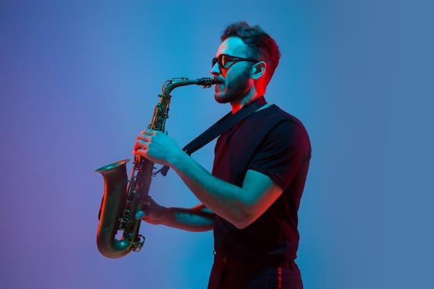 グラデーションブルーパープルスタジオでサックスを演奏する若い白人ジャズミュージシャン