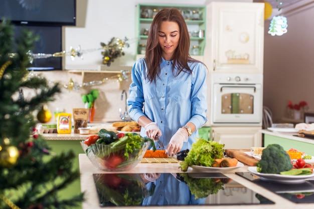 집에서 장식 된 부엌에서 새해 또는 크리스마스 식사를 요리하는 젊은 백인 아가씨