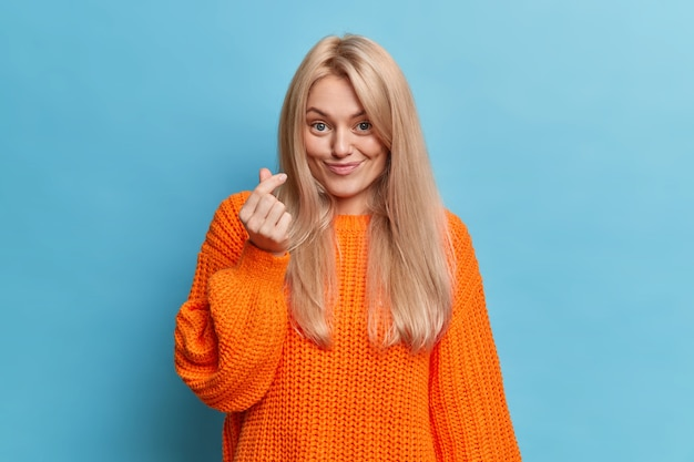 Young caucasian lady shows mini heart hand gesture has pleasant smile dressed in casual orange jumper