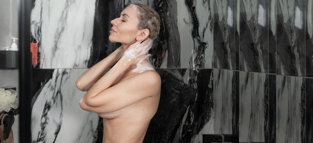 젊은 백인 아가씨는 샤워를합니다. 머리를 감는다. 몸과 모발 관리. 측면보기, 배너