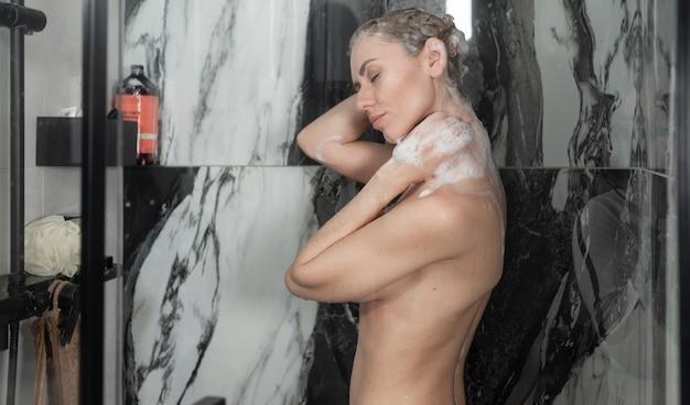 젊은 백인 아가씨는 샤워를합니다. 머리를 감는다. 몸과 모발 관리. 측면보기,