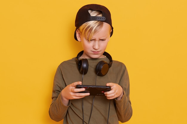 Young caucasian little boy using mobile phone against yellow, guy looks concentrated, holding his mobile phone