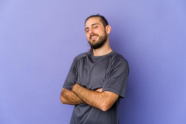 Молодой кавказский человек с длинными волосами изолирован, выражая эмоции