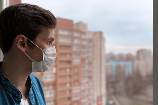 Молодой кавказский главный в защитной маске остается в изоляции дома для самостоятельного карантина, глядя в окно.