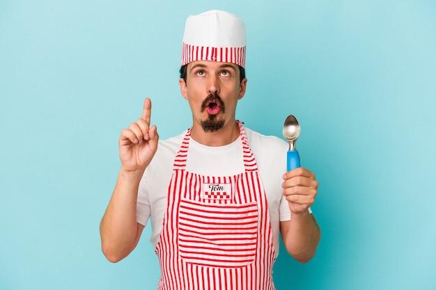 口を開けて逆さまを指している青い背景に分離されたスクープを保持している若い白人メーカー。