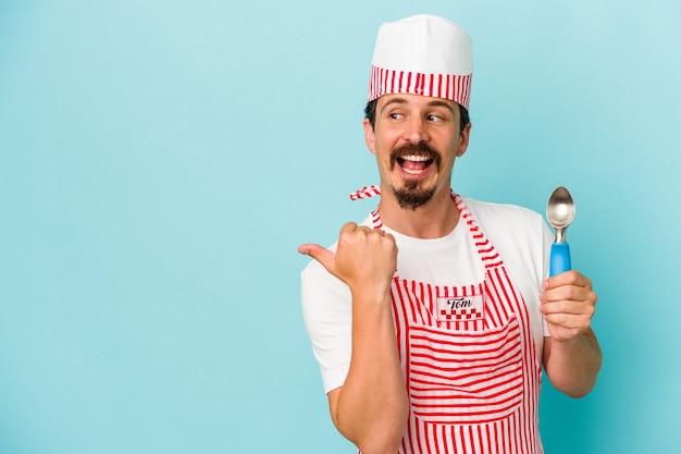 青い背景のポイントで隔離されたスクープを親指の指で離して、笑ってのんきな若い白人メーカー。
