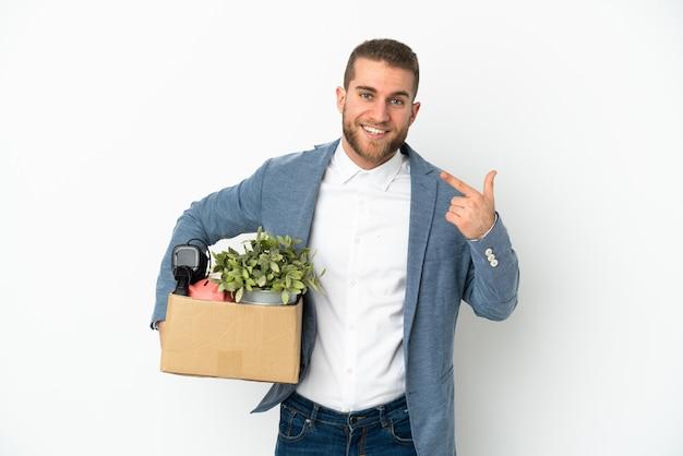 Молодой кавказец делает движение, поднимая коробку, полную вещей, изолированную на белом фоне, показывая жест пальца вверх