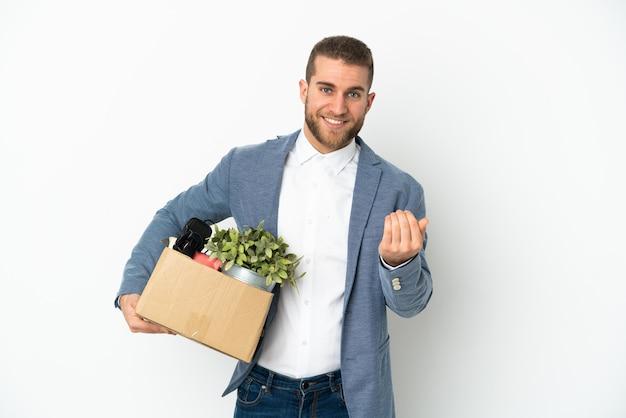Молодой кавказец делает ход, поднимая коробку, полную вещей, изолированных на белом фоне, приглашая прийти с рукой. счастлив что ты пришел Premium Фотографии