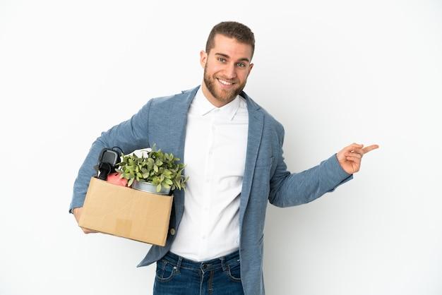 Молодой кавказец делает ход, поднимая коробку, полную вещей, изолированную на белом фоне, указывая пальцем в сторону