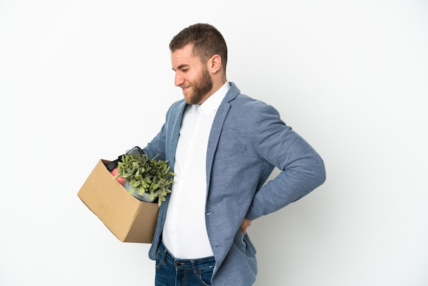 Молодой кавказец делает движение, поднимая коробку, полную вещей, изолированную на белом фоне, страдает от боли в спине из-за того, что приложил усилие