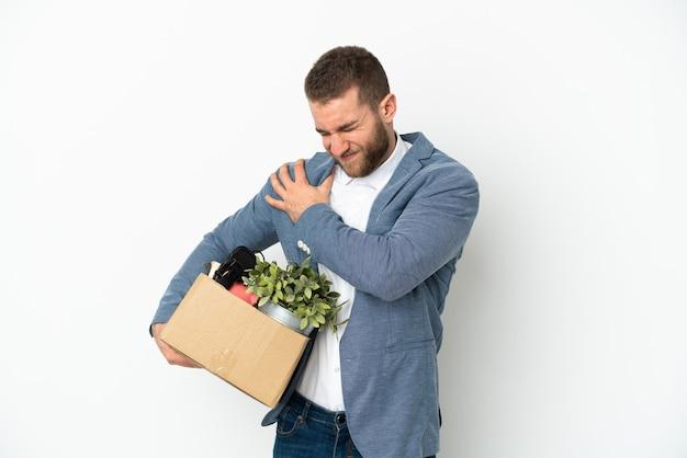 Молодой кавказец делает движение, поднимая коробку, полную вещей, изолированную на белом фоне, страдая от боли в плече из-за того, что приложил усилие