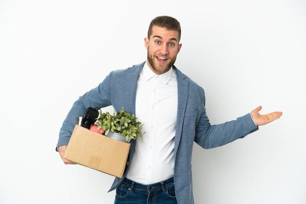 Молодой кавказец делает движение, поднимая коробку, полную вещей, изолированную на белом фоне с шокированным выражением лица