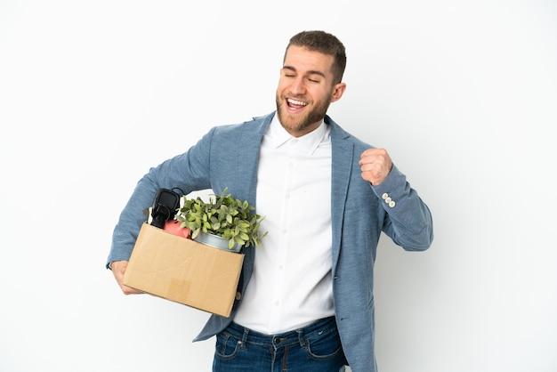 Молодой кавказец делает движение, поднимая коробку, полную вещей, изолированную на белой стене, празднуя победу