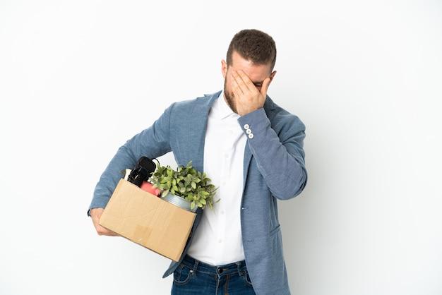 Молодой кавказец делает движение, поднимая коробку, полную вещей, изолированную на белой стене, с усталым и больным выражением лица
