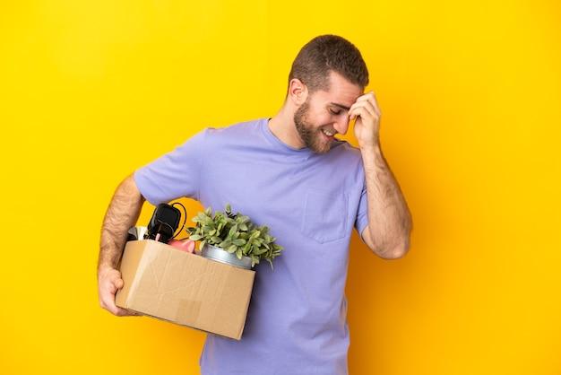 Молодой кавказец делает ход, поднимая коробку, полную вещей, изолированную на желтом фоне, смеясь