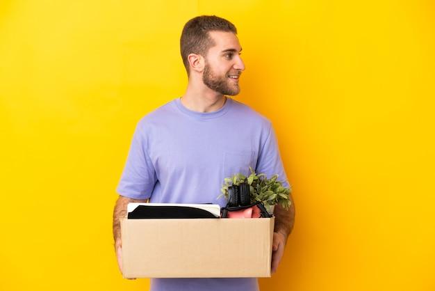 Молодой кавказец делает движение, поднимая коробку, полную вещей, изолированную на желтой стороне