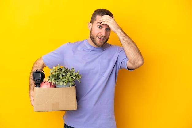 측면을 보면서 깜짝 제스처를 하 고 노란색 벽에 고립 된 것의 전체 상자를 집어 들고 젊은 백인 이동