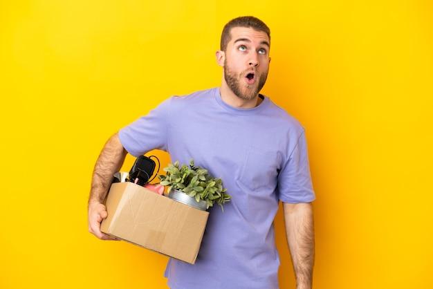 노란색 벽에 고립 된 물건으로 가득 찬 상자를 집어 들고 놀란 표정으로 움직이는 젊은 백인