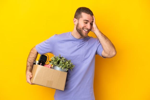 Молодой кавказец делает движение, поднимая коробку, полную вещей, изолированную на желтой стене, много улыбаясь