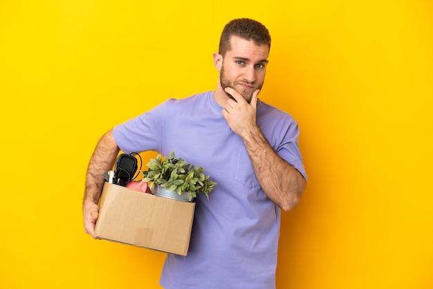 노란색 벽 생각에 고립 된 것의 전체 상자를 집어 들고 젊은 백인 이동