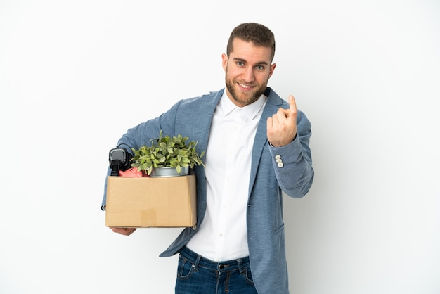 Young caucasian making a move while picking up a box full of things isolated on white background doing coming gesture