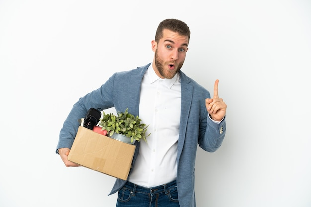 Young caucasian making a move while picking up a box full of things isolated on white background intending to realizes the solution while lifting a finger up