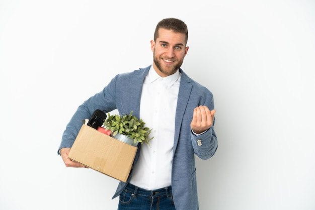 Young caucasian making a move while picking up a box full of things isolated on white background inviting to come with hand. happy that you came