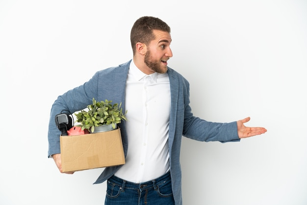 Young caucasian making a move while picking up a box full of things isolated on white background with surprise expression while looking side
