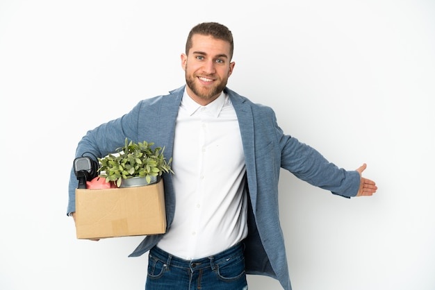 Young caucasian making a move while picking up a box full of things isolated on white extending hands to the side for inviting to come