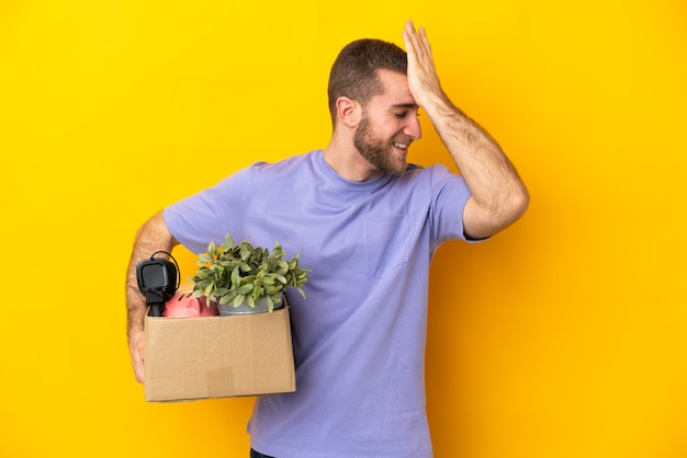 Young caucasian making a move while picking up a box full of things isolated on yellow background has realized something and intending the solution