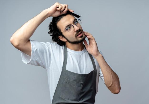 眼鏡と波状のヘアバンドを身に着けている若い白人男性の理髪師は、あごに触れて、コピースペースで白い背景で隔離された側を見て均一な櫛の髪で