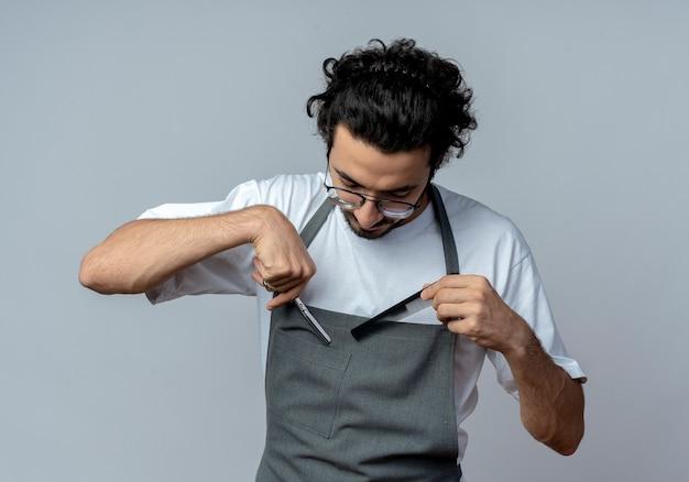 眼鏡と波状の髪のバンドを身に着けている若い白人男性の理髪師は、白い背景で隔離の彼のポケットから見下ろしているハサミと櫛を引っ張る均一に