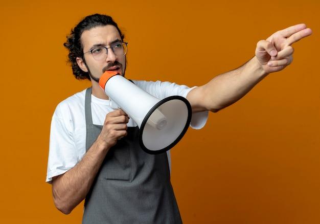 Молодой кавказский парикмахер в очках и с волнистой лентой для волос в униформе, говорящий оратором, смотрящим и указывая в сторону