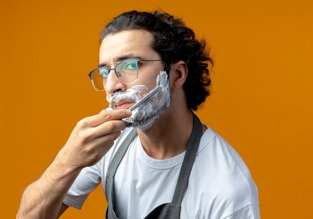 Giovane barbiere maschio caucasico con gli occhiali e fascia per capelli ondulati in uniforme che guarda e si rade la barba con un rasoio a mano libera con crema da barba messa sul viso