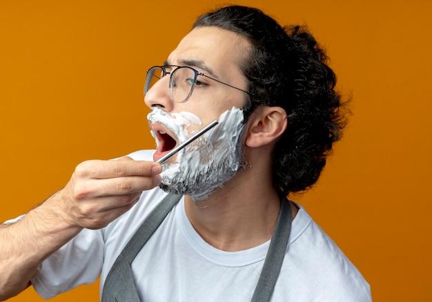 Giovane barbiere maschio caucasico con gli occhiali e fascia per capelli ondulati in uniforme che rade la propria barba con rasoio a mano libera con crema da barba messa sul viso guardando dritto con la bocca aperta