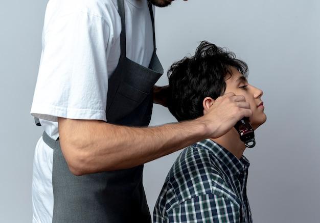 Giovane maschio caucasico barbiere con gli occhiali e fascia per capelli ondulati in uniforme in piedi in vista di profilo facendo taglio di capelli per il suo giovane cliente su sfondo bianco