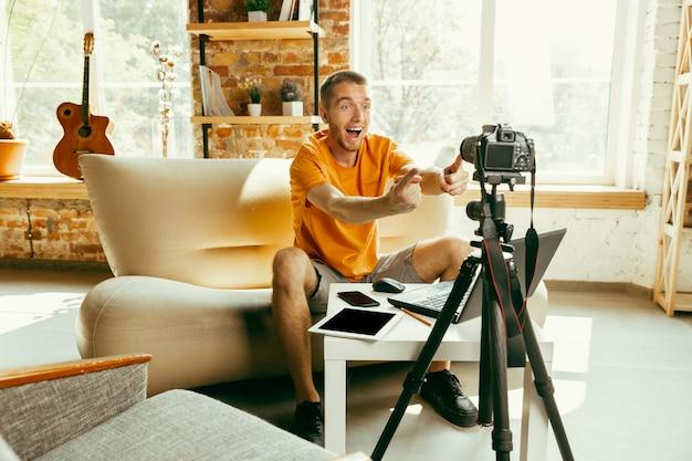 Giovane blogger maschio caucasico con videocamera professionale che registra video recensione di gadget a casa