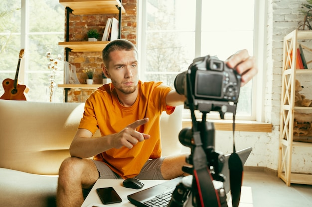 Young caucasian male blogger with professional camera recording video review of gadgets at home