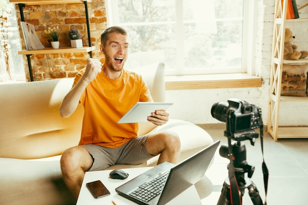 집에서 태블릿의 전문 카메라 녹화 비디오 검토와 젊은 백인 남성 블로거