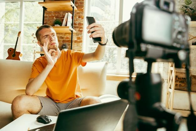 Giovane blogger maschio caucasico con videocamera professionale che registra video recensione di smartphone a casa