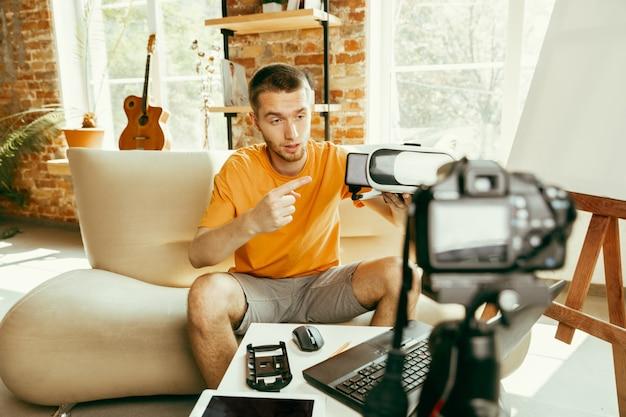 Молодой кавказский блоггер-мужчина с профессиональным оборудованием, записывающий видеообзор очков vr дома. блог, видеоблог, видеоблог. мужчина оценивает гарнитуру виртуальной реальности во время потоковой передачи в прямом эфире.