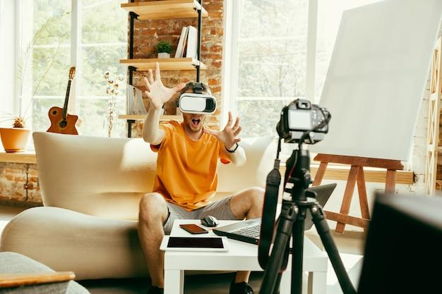 Giovane blogger maschio caucasico con attrezzatura professionale che registra video recensione di occhiali vr a casa. blogging, videoblog, vlogging. uomo che utilizza le cuffie da realtà virtuale durante lo streaming live.
